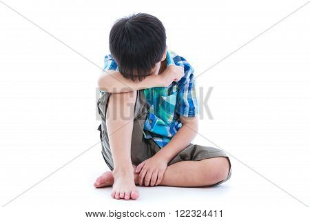 Little sad boy barefeet sitting on floor. Isolated on white background. Negative human emotions. Conceptual about children who lack warmth and affection abandoned children.