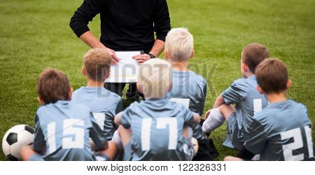 Coach Encouraging Boys Soccer Team. Soccer Football Team with Coach at the Stadium. Coach with Youth Soccer Team. Boys Listen to Coach's Instructions. Coach Giving Team Talk