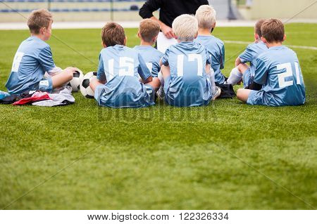 Soccer Football Team with Coach at the Stadium. Coach with Youth Soccer Team. Boys Listen to Coach's Instructions. Coach Giving Team Talk