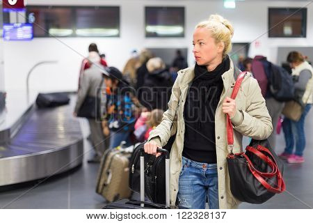 Casually dressed young female traveller waiting in airport arrival terminal hall,  collecting her laggage . Blured background. Can also be used as railway, metro, bus station.