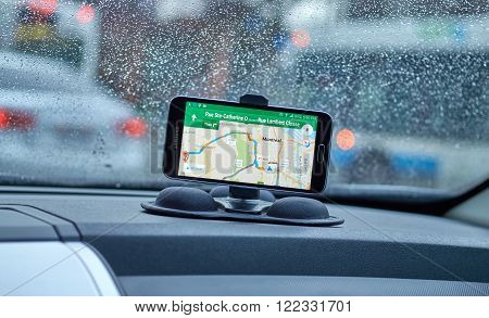 MONTREAL CANADA - MARCH 15 2016 - GPS application Google Maps on Samsung S5 im a car over wet windows background. Google Maps is one of the most popular GPS applications.
