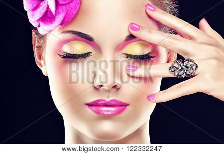 A fashion image model .Trend bright pink makeup . Stylish model girl with pink manicure nails and with  clip on his head   .Jewelry ring