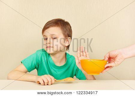 Little discontented boy refuses to eat a porridge