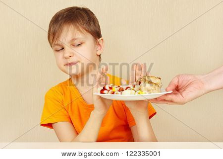 Little disaffected boy refuses to eat a pasta with cutlet