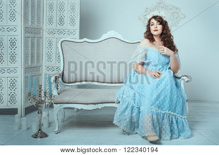 Beautiful woman with overweight sitting on the sofa in the room.
