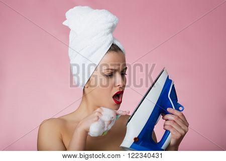 Pretty woman with bath towel and flatiron