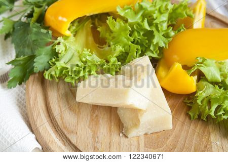 Parmigiano (parmesan) cheese around fresh yellow pepper lettuce leaves parsley on wooden board and napkin background