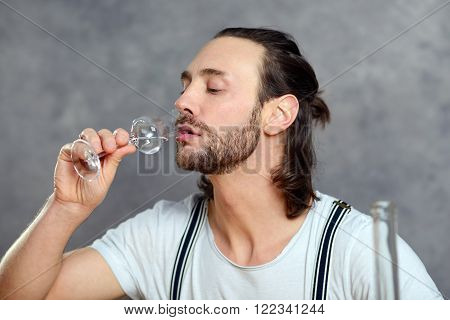 young man in front of gray background drinking clear spirit