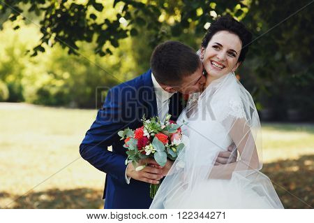 Happy Couple Of Newlyweds, Bride And Groom Kissing & Hugging In Park