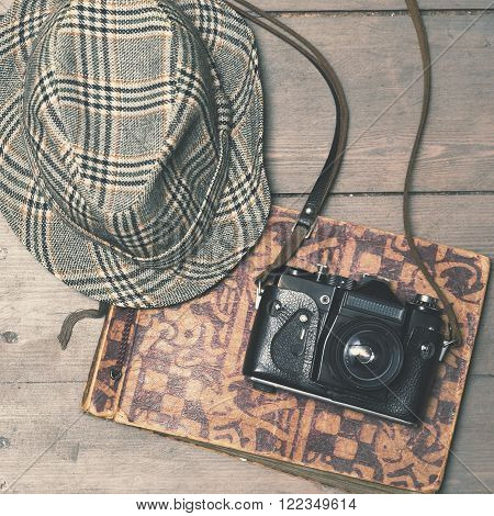 retro camera with vintage trilby hat and photo album on wooden background