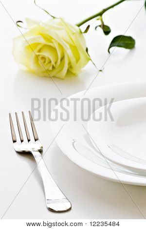 place setting with white plates and rose flower