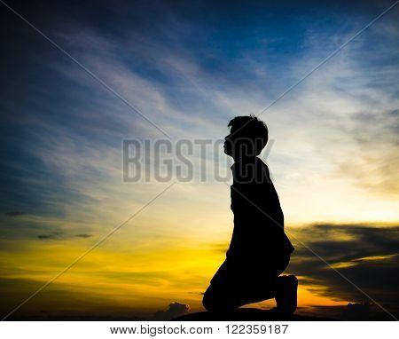 praying man kneel on beautiful sky background
