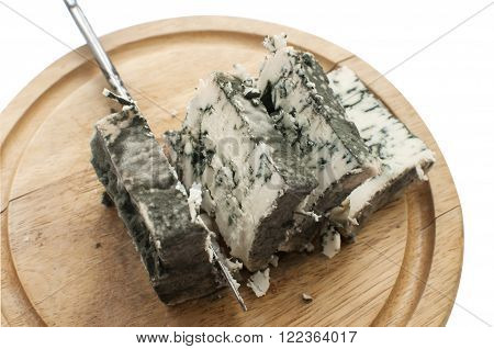 Sliced moldy lump of white cheese and knife on wooden tray isolated on white background