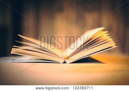 Open aged book on wooden desktop and wooden wall in the background. Side view