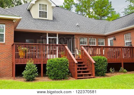 Wooden deck in the back of a brick residential house