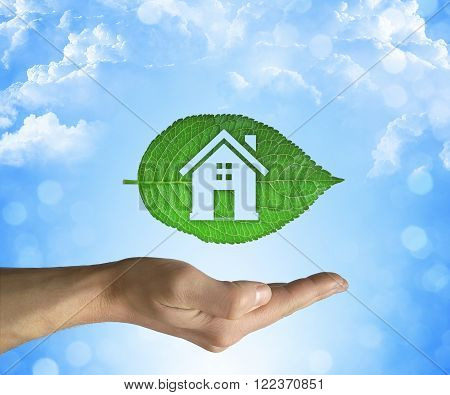 Opened hand holding a green leaf with a house icon inside on a blue sky background. Eco house concept