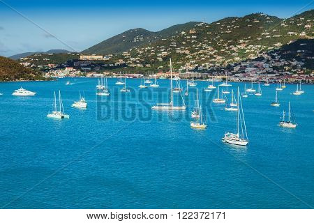 Harbor in St. Thomas, U.S. Virgin Islands, with sailboats and tropical island.