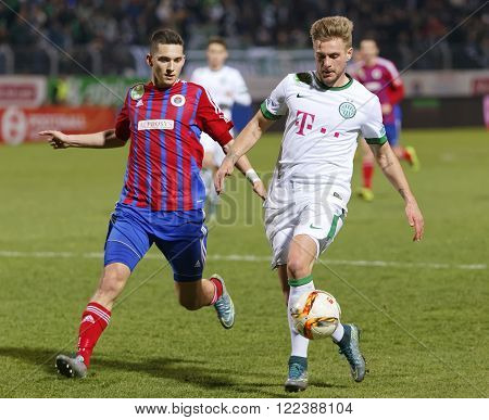 BUDAPEST HUNGARY - MARCH 19 2016: Mate Vida of Vasas (l) follows Florian Trinks of Ferencvaros during Vasas - Ferencvaros OTP Bank League football match at Illovszky Stadium.