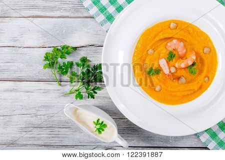 Pumpkin bisque With Prawns and chick pea top view
