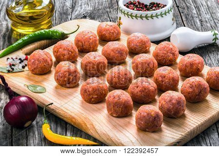 raw meatball on a cutting board prepared for cooking close-up