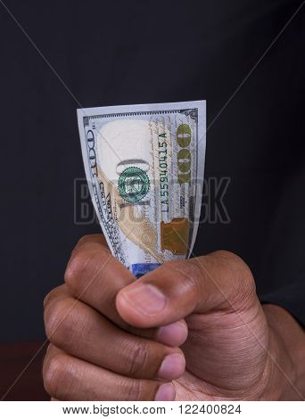 Hand Holding tight grip on a 100 Dollar Bill