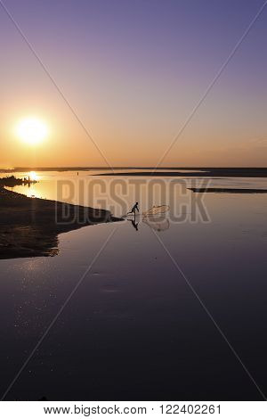 Sunset silhouette of a fisherman on the Brahmaputra River in Arunachal Pradesh, India.