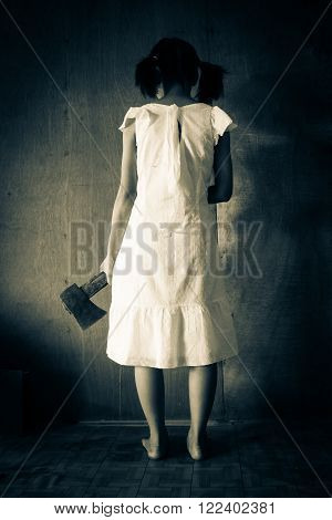 Ghost girl in haunted house,Mysterious girl in white dress standing in abandon house carrying an axe in front of the wall