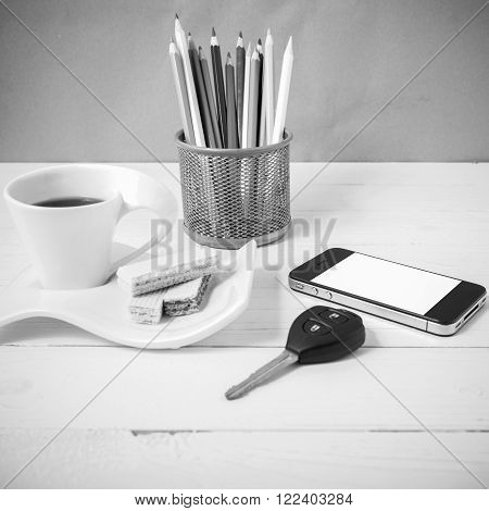 coffee cup with waferphonepencil boxcar key on white wood background black and white color