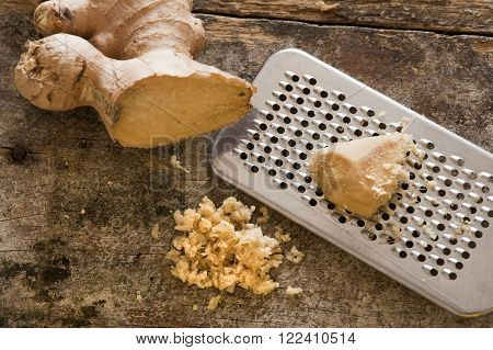 Fresh ginger root, shavings and stainless steel grater over old worn out wooden table