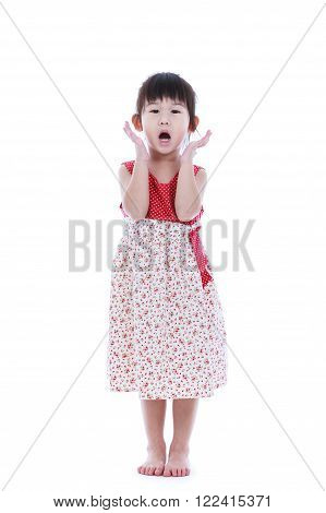 Wow. Full body of an adorable little asian girl in beautiful dress holding her mouth opened, hands on cheek and looking at camera. Studio shot. Isolated on white background.
