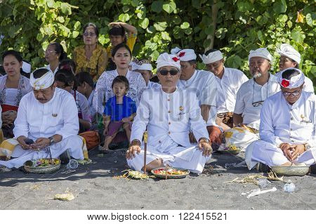 UBUD, BALI, INDONESIA - MARCH 19, 2015 : Unidentified Indonesian people celebrate Balinese New Year and the arrival of spring. People praying at Ketewel beach during the religious ceremony