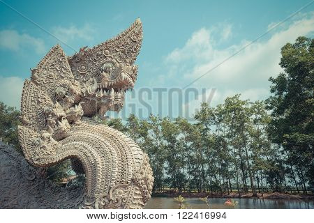 Serpent or naga statue head with blue sky background