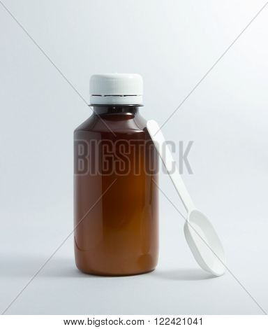 Brown bottle of cough syrup with white plastic spoon isolated on white background