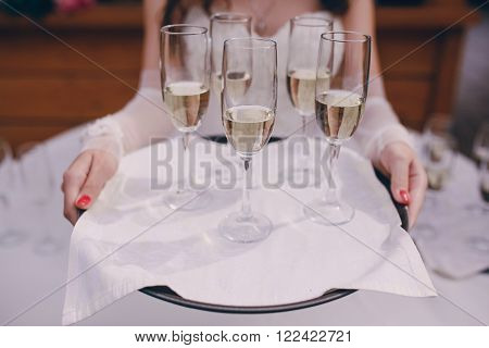 glasses at a wedding in the hands of the waiter with champagne