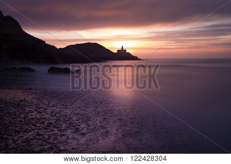 Good morning Bracelet Bay Sunrise at Bracelet Bay, featuring Mumbles Lighthouse in Swansea, South Wales