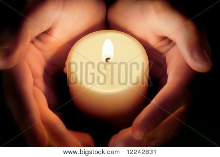 hands protecting the glowing flame of a candle in the darkness poster