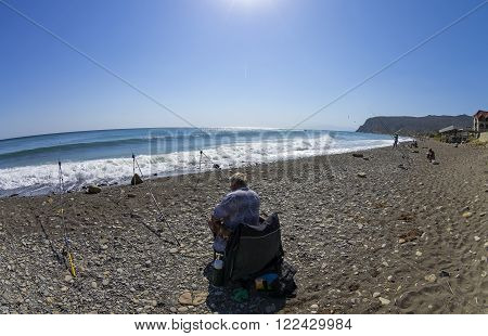 Crimea September 9 2014. Sea fishing. A fisherman with a fishing rod on a deserted beach.