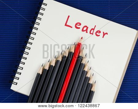 Red pencil standout from black pencil and handwriting word Leader on blank notebook with blue corrugate paper background, leadership business concept