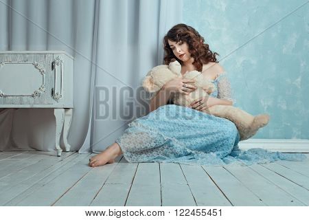 Woman sitting on the floor in the room on the hands is a toy bear.