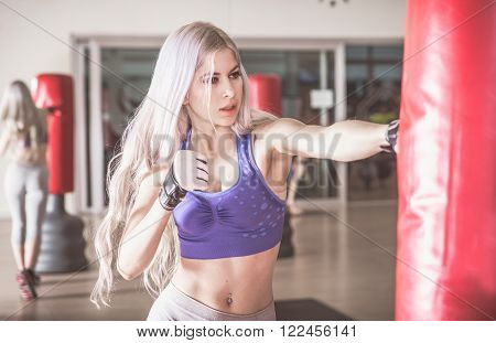 Woman fighter hit the heavy boxing bag ** Note: Shallow depth of field