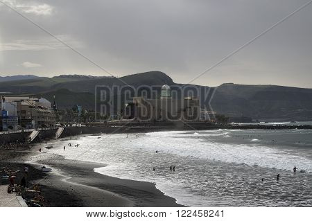 LAS PALMAS GRAN CANARIA SPAIN - NOVEMBER 14 2015: local life at Las Canteras beach with Alfredo Kraus Auditorium in the background