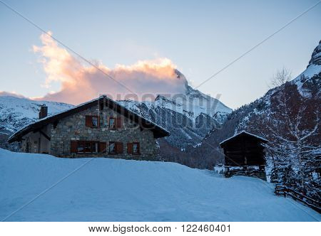 Stone Swiss chalet with the Matterhorn in the background engulfed in clouds, in the Swiss Alps