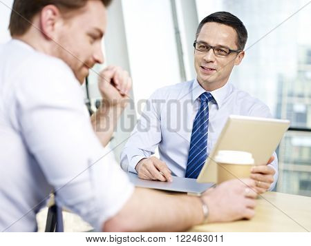 two caucasian corporate executives sitting at desk having a discussion in office.