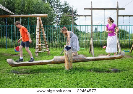 Mother with son and daughter teetering on a swing on a wooden playground
