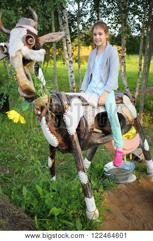A girl sits astride a stylized cow from exposure in Russian park