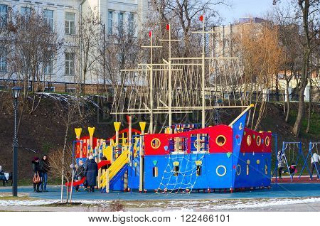 GOMEL BELARUS - MARCH 6 2016: Unidentified people are at children's playground at the new site of the embankment of the river Sozh Gomel Belarus