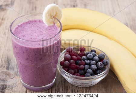 Smoothie of banana berries frozen cranberries and blueberries with yogurt.