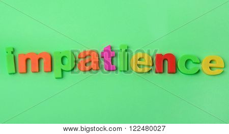 Colorful letters Impatience word on green background