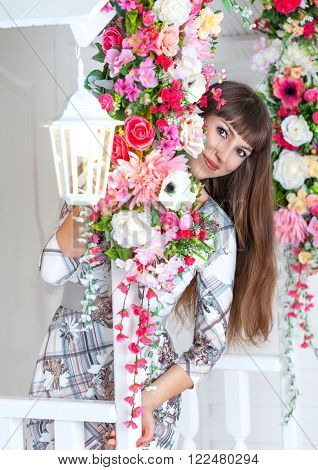 Young beautiful woman hides among tsvetov.Fasad white house with a floral composition foarem street with a floral composition with a porch and railing.