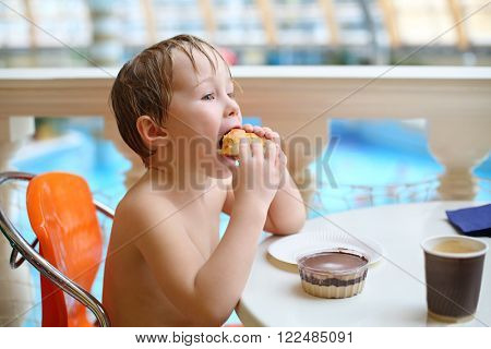 Little boy eating a bun and chocolate pudding in a cafe in the waterpark